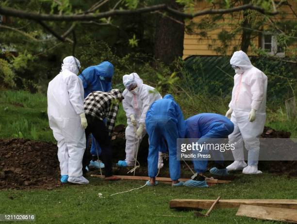 Medical staff and relatives wearing protective gear bury the body of a man who died from the coronavirus disease at a graveyard in Qazipora Village...