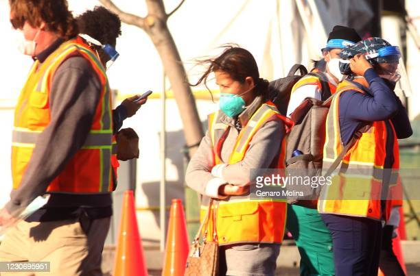 Medical staff and workers deal with cold winds while giving vaccines against COVID-19 at California State University Northridge in Northridge on...