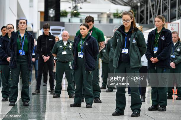 Medical staff at the Louisa Jordan hospital stand during a UK wide minutes silence to commemorate the key workers who have died with coronavirus on...