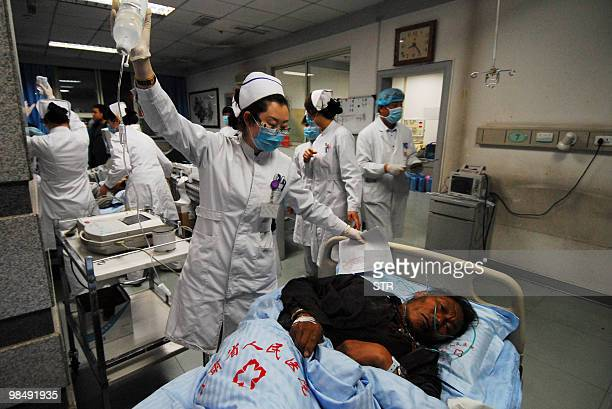 Medical staff attend to an injured earthquake victim at a hospital after a group of 24 severely injured surviors were evacuated to Lanzhou, in...