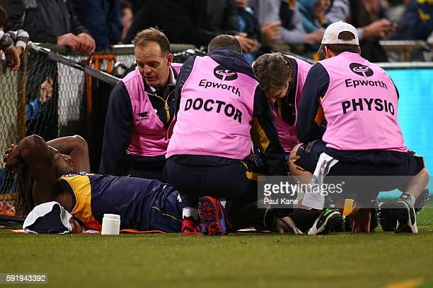Medical staff attend to Nic Naitanui of the Eagles after injurying his leg during the round 22 AFL match between the West Coast Eagles and the...