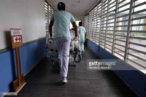 Medical staff carry a Covid-19 patient in the intensive care unit of the hospital of Saint-Pierre, on the French Indian Ocean island of La Reunion on...