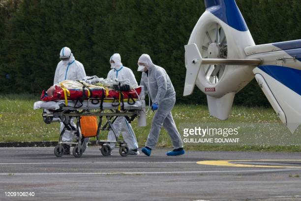 Medical staff carry a COVID19 patient on a stretcher after an evacuation by helicopter from the IledeFrance region at the Trouseau university...