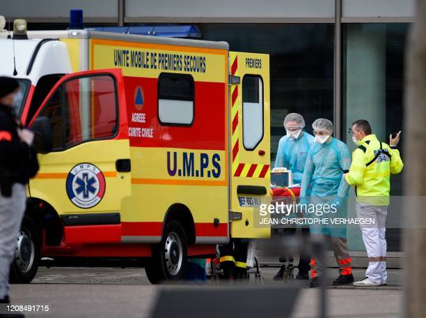 Medical staff carry a patient infected with the novel coronavirus on a stretcher in Nancy, eastern France, prior to his transfer into a medicalised...
