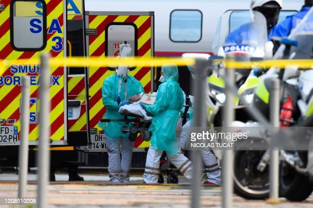 Medical staff carry a patient infected with the novel coronavirus on a stretcher at the Saint-Jean train station in Bordeaux, southwestern France, on...