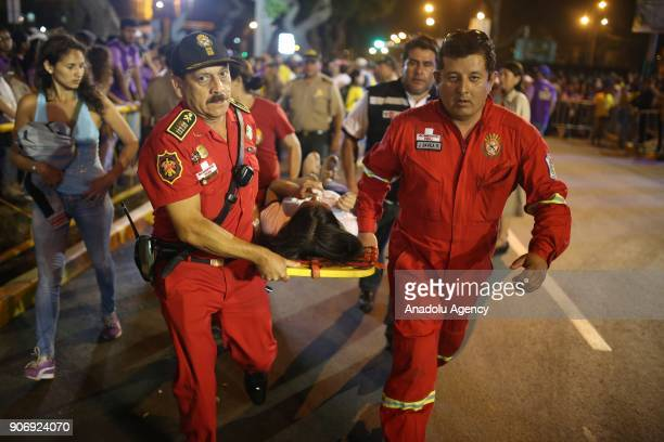 Medical staff carry a woman who fell ill as she was waiting to welcome Pope Francis on a stretcher in Lima Peru on January 18 2018