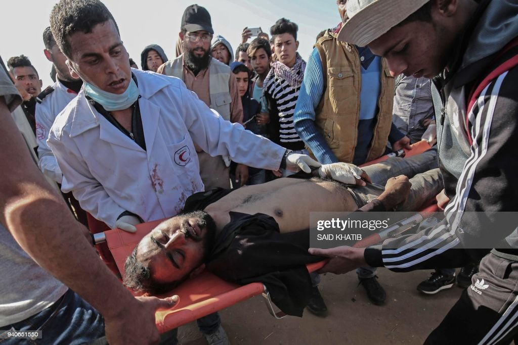Medical staff carry an injured Palestinian man at an emergency medical tent after clashes with Israeli security forces after a demonstration near the border with Israel, east of Khan Yunis, in the southern Gaza Strip, on April 01, 2018. /