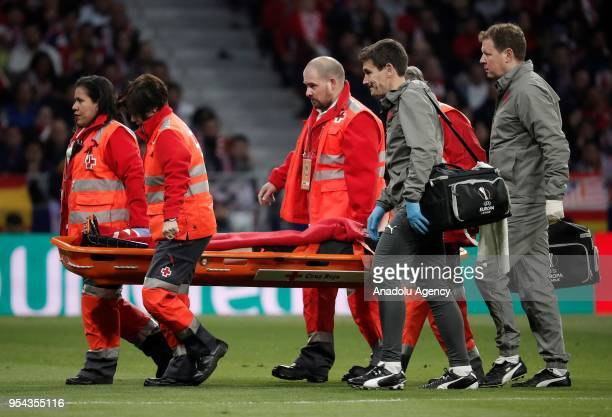 Medical staff carry Laurent Koscielny of Arsenal after he was injured during the UEFA Europa League semi final return match between Atletico Madrid...