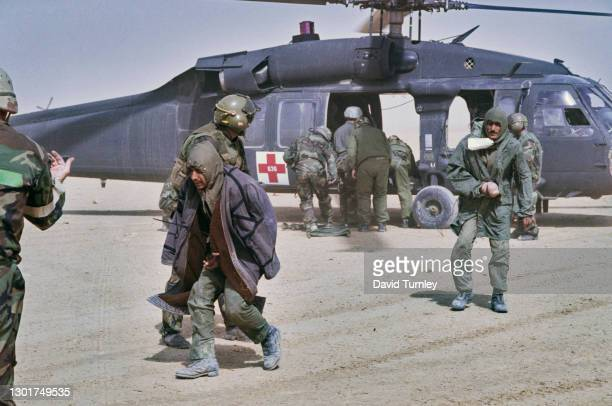 Medical staff carrying injured United States Military personnel from a Sikorsky UH-60 Black Hawk helicopter at the 5th Mobile Army Surgical Hospital,...