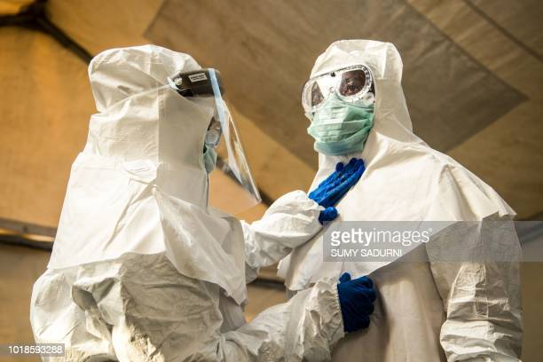 TOPSHOT Medical staff check each others protective suits before entering the isolation unit at a hospital in Bundibugyo western Uganda on August 17...