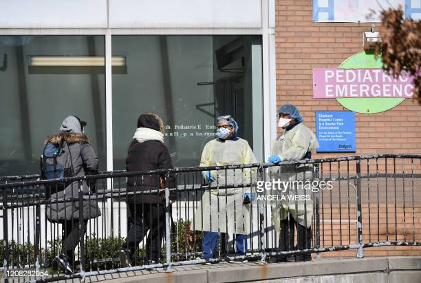 Medical staff check in people to get tested for the coronavirus at Elmhurst Hospital Center in the Queens borough of New York City on March 26 2020...