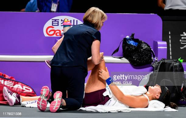 A medical staff checks the knee of Bianca Andreescu of Canada during her women's singles match against Karolina Pliskova of Czech Republic in the WTA...