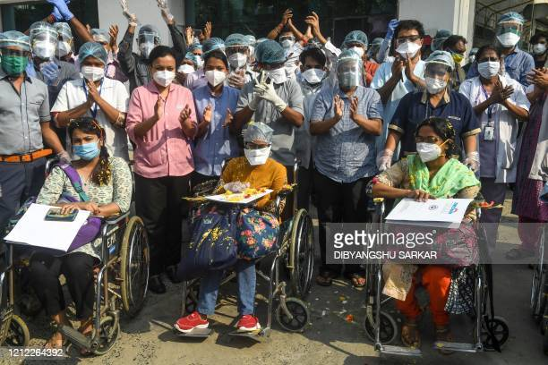 Medical staff cheer along with recovered COVID-19 coronavirus patients as they come out of a private hospital, in Kolkata on May 9, 2020.