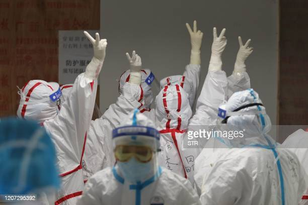 Medical staff cheer themselves up before going into an ICU ward for COVID-19 coronavirus patients at the Red Cross Hospital in Wuhan in China's...