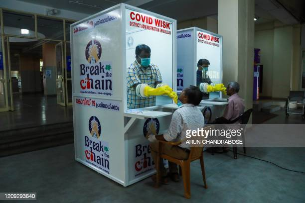 Medical staff collect samples from people at newly set upped Walk-In Sample Kiosk to test for the COVID 19 coronavirus at Ernakulam Medical College...