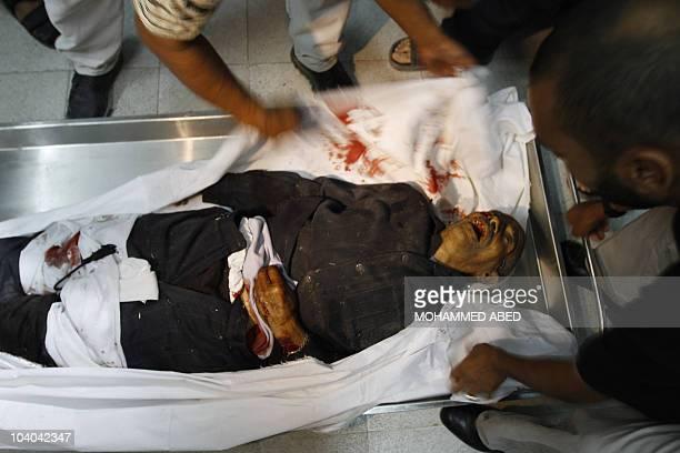Medical staff cover the body of 91yearold Palestinian farm caretaker Ibrahim Abdullah Abu Saeed killed on September 12 2010 by Israeli gunfire in the...