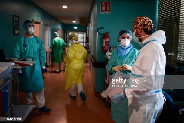 Medical staff discuss as a sociomedical worker is pictured during her shift at the Cremona hospital's COVID19 intensive therapy area on April 22 2020...