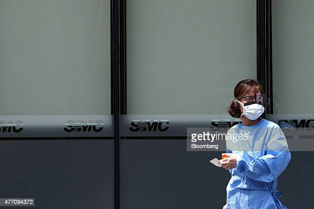 A medical staff employee wearing a mask walks past a closed hospital emergency room at the Samsung Medical Center in Seoul South Korea on Sunday June...