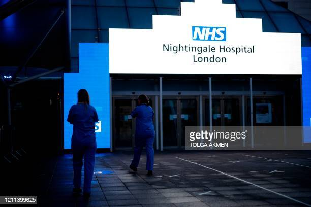Medical staff from Britain's NHS in scrubs walk outside the ExCeL London exhibition centre which has been transformed into the NHS Nightingale field...