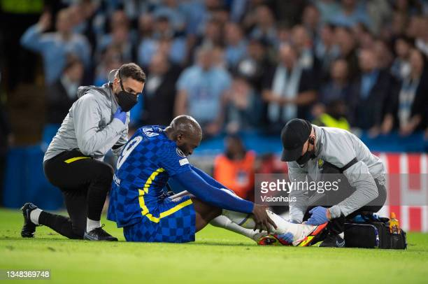 Medical staff from Chelsea help as Romelu Lukaku holds his ankle after being injured whilst being tackled during the UEFA Champions League group H...
