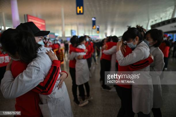 TOPSHOT Medical staff from Jilin Province hug nurses from Wuhan after working together during the COVID19 coronavirus outbreak during a ceremony...