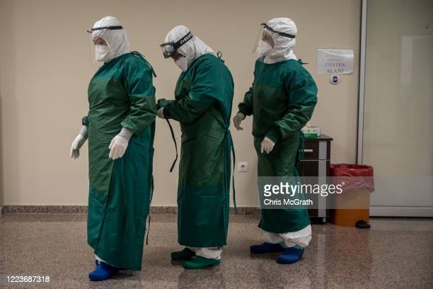 Medical staff get dressed in personal protective equipment before cleaning and disinfecting a bed after a COVID-19 patient was discharged from the...