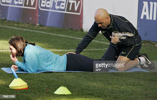 A medical staff gives a massage to FC Barcelona's Argentinian striker Lionel Messi who tore a muscle in his left thigh during a match against...