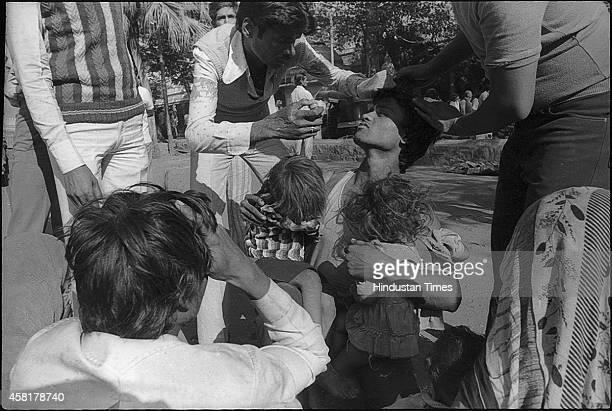 A medical staff giving eye drops to a victim of Bhopal gas tragedy on a roadside on December 4 1984 in Bhopal India on December 4 1984 in Bhopal...
