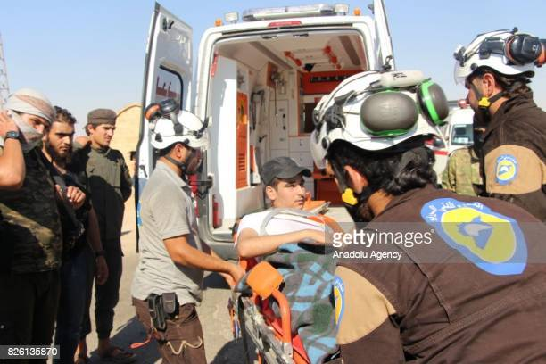 Medical staff help an injured man get off an ambulance after a ceasefire announced between Hezbollah and Ahrar alSham in Idlib Syria on August 03...