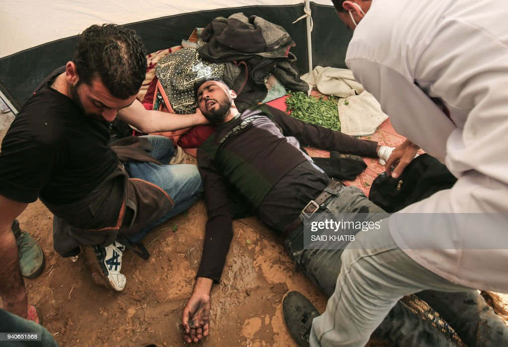 Medical staff help an injured Palestinian man at an emergency medical tent after clashes with Israeli security forces after a demonstration near the border with Israel, east of Khan Yunis, in the southern Gaza Strip, on April 01, 2018. /