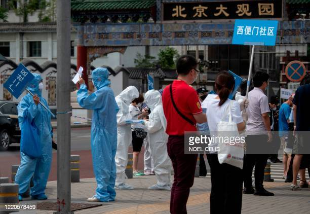 TOPSHOT Medical staff in full protective gear carry signs to assist people who live near or who have visited the Xinfadi Market a wholesale food...