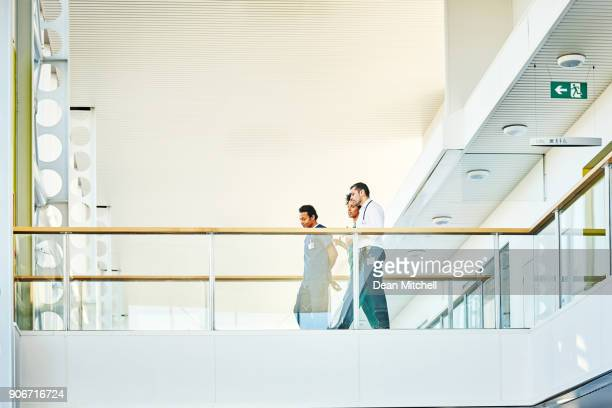 medical staff in modern hospital building - general hospital stock photos and pictures