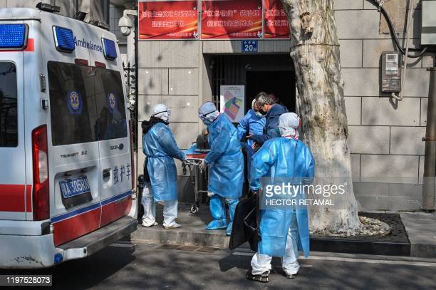 Medical staff in protective clothes are seen carrying a patient from an apartment suspected of having the virus in Wuhan, in Hubei province on...