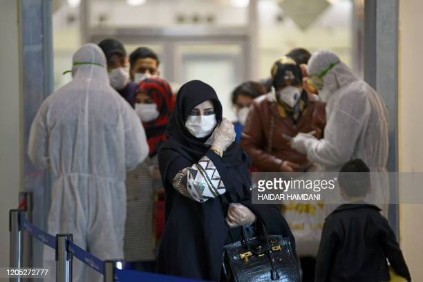 Medical staff in protective gears distribute information sheets to Iraqi passengers returning from Iran at Najaf International Airport on March 5,...