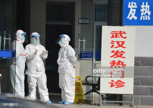 Medical staff in protective outfit wait for patients at the entrance to the clinic for fever or Wuhan-related patients in a hospital in Fuyang in...