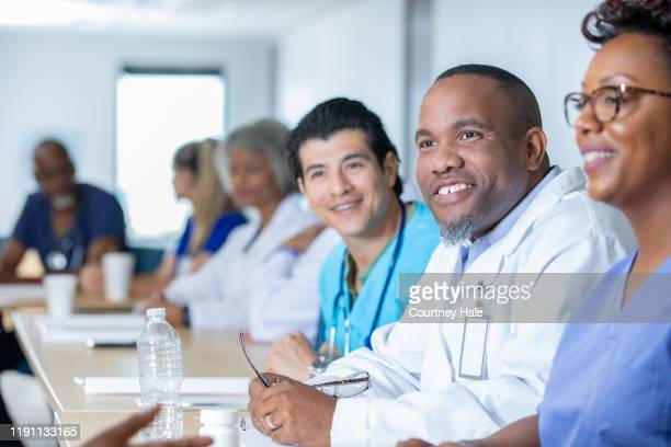 medical staff meeting in conference room - civilian stock pictures, royalty-free photos & images