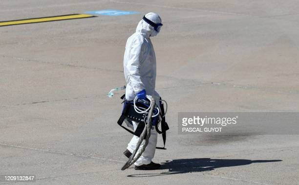 Medical staff member carries an artificial respirator during the arrival by helicopter of a patient infected with the COVID-19, at the Nimes air...