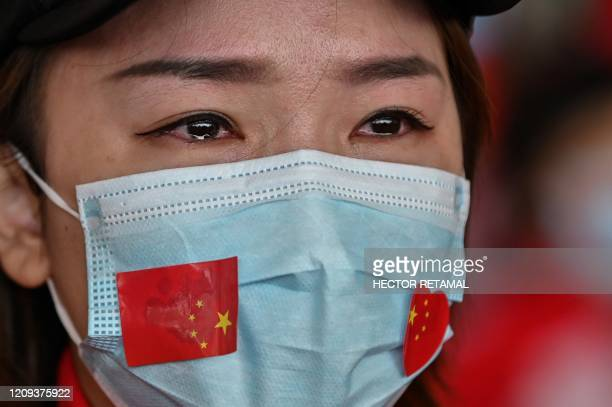 TOPSHOT A medical staff member from Jilin Province tears up during a ceremony before leaving as Tianhe Airport is reopened in Wuhan in China's...