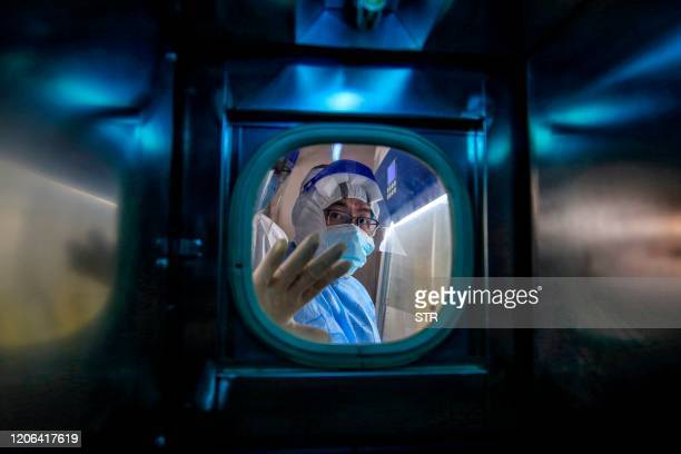 TOPSHOT A medical staff member gestures inside an isolation ward at Red Cross Hospital in Wuhan in China's central Hubei province on March 10 2020...