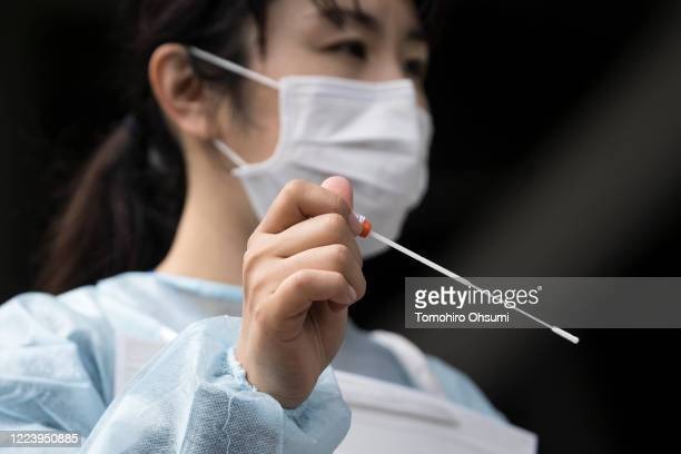 Medical staff member holds a cotton swab for a COVID-19 polymerase chain reaction test during a rehearsal at a testing site outside Kashima Soccer...