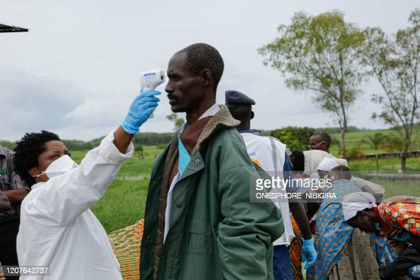 Medical staff member measures a man's temperature as a preventive measure against the COVID-19 coronavirus on his arrival of repatriation in Gatumba,...