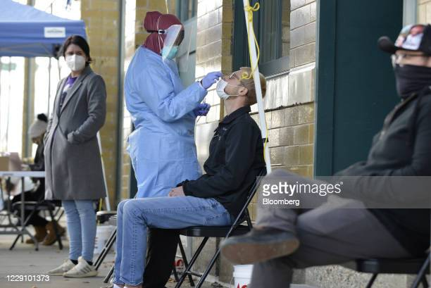 Medical staff member performs a Covid-19 test outside the Family Healthcare building in downtown Fargo, North Dakota, U.S., on Thursday, Oct. 15,...