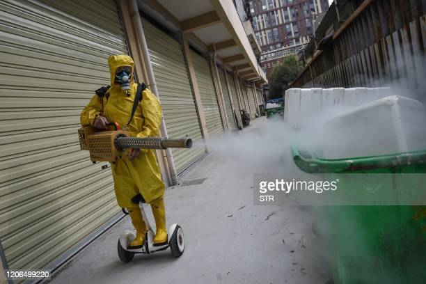 TOPSHOT A medical staff member sprays disinfectant at a residential area in Wuhan in China's central Hubei province on March 11 2020 China reported...
