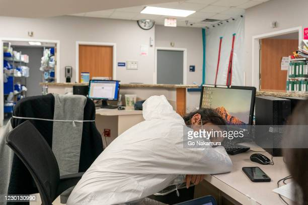 Medical staff member Stephanie takes a short nap in nursing station in the COVID-19 intensive care unit at the United Memorial Medical Center on...