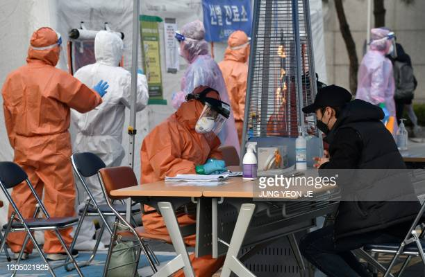 Medical staff member talks with a man with suspected symptoms of the COVID-19 coronavirus, at a testing facility in Seoul on March 4, 2020. - South...