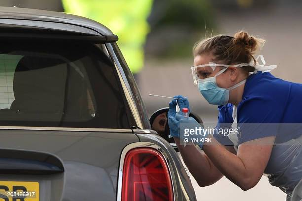 Medical staff member tests an NHS worker for the novel coronavirus COVID-19 at a drive-in facility set up in the carpark of Chessington World of...
