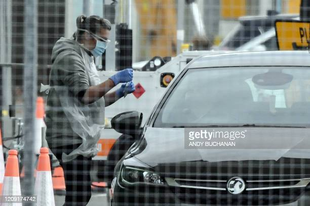 A medical staff member wearing gloves eye protection and a face mask tests an NHS worker for the novel coronavirus COVID19 at a drivein facility set...