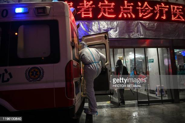 A medical staff member wearing protective clothing to help stop the spread of a deadly virus which began in the city is seen on a ambulance at the...