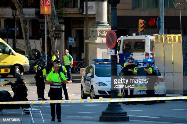 TOPSHOT Medical staff members and policemen stand in a cordoned off area after a van ploughed into the crowd injuring several persons on the Rambla...