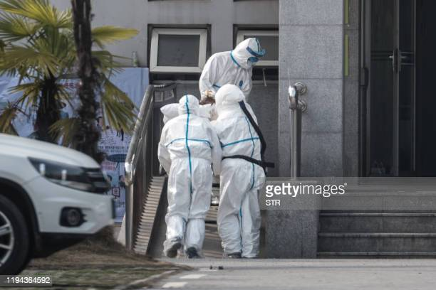 Medical staff members carry a patient into the Jinyintan hospital where patients infected by a mysterious SARSlike virus are being treated in Wuhan...